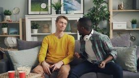 I tipi allegri stanno giocando il video gioco a casa che esprime le emozioni e rilassandosi sul sofà che gode della tecnologia mo video d archivio