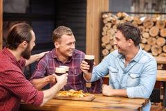 I tipi attraenti stanno godendo della bevanda dell'alcool in pub Fotografie Stock