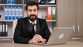 I tipi dell'uomo d'affari sul computer poi esamina la macchina fotografica e sorride video d archivio