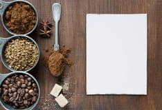 I tipi differenti di caffè e di carte bianche sono su un backgro di legno Immagine Stock