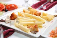 I tipi differenti di formaggi si trovano su un piatto bianco Immagine Stock Libera da Diritti