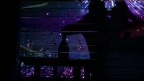I tipi e le ragazze felici ballano e bevono l'alcool dentro nella sera in una stanza scura video d archivio