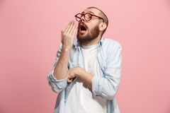 Beautiful bored man bored  on pink background. I am tired of everything. Bored man. Boring, dull, tedious concept. Young caucasian emotional man. Human emotions Royalty Free Stock Photo
