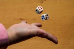 I tiri della mano tagliano per giocare un gioco da tavolo su un fondo nero Fotografie Stock