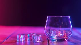 I tomt exponeringsglas fallande iskuber studsa sig F?rgbelysning closeup arkivfilmer