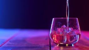 I torktumlare med is som står på tabellen, hällde skotsk whisky Kameraflyttningar lager videofilmer