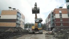 I trasporti gialli dell'escavatore sulla botola concreta delle catene suonano al cantiere stock footage