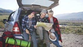 I tre amici felici stanno esaminando il programma di strada mentre si sedevano davanti al tronco di automobile di viaggio con il  video d archivio