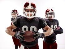 I tre giocatori di football americano che posano con la palla su fondo bianco immagine stock libera da diritti