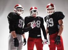 I tre giocatori di football americano che posano con la palla su fondo bianco fotografia stock