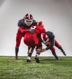 I tre giocatori di football americano nell'azione immagini stock