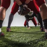 I tre giocatori di football americano nell'azione fotografia stock