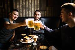 I tre giovani in abbigliamento casual sono sorridenti e risuonare i vetri della birra insieme mentre si siedono nel pub Fotografie Stock