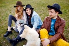 I tre giovani alla moda passano insieme il tempo all'aperto con il loro cane del husky che si siede sull'erba verde fotografie stock libere da diritti