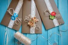 I tre pezzi di carta marrone con il pezzo di cotone merlettano con il fiore di carta Fotografie Stock Libere da Diritti