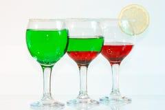 I tre vetri di liquore e del lemo verdi e rossi Fotografia Stock