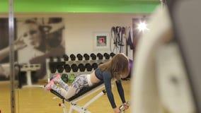 I treni della ragazza nella palestra con le teste di legno Addestramento di forza Forma fisica femminile archivi video