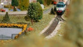 I treni di modello ed il tram del carico che passano da, si incontrano ed attraversano su un diorama stock footage