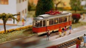 I treni di modello transitano e un tram parte su un diorama, fine su stock footage