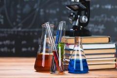 I tubi con i liquidi chimici stanno su una tavola di legno su un chalkbo Immagine Stock Libera da Diritti