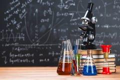 I tubi con i liquidi chimici stanno su una tavola di legno su un chalkbo Immagini Stock Libere da Diritti