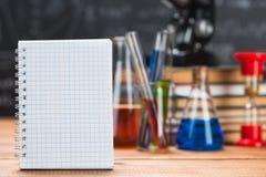 I tubi con i liquidi chimici stanno su una tavola di legno su un chalkbo Fotografia Stock Libera da Diritti