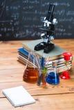 I tubi con i liquidi chimici stanno su una tavola di legno su un chalkbo Immagini Stock