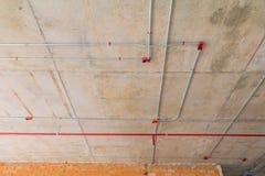 I tubi del metallo in spruzzatore del fuoco e della costruzione sul tubo rosso stanno pendendo dall'interno del soffitto Fotografia Stock Libera da Diritti