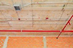 I tubi del metallo in spruzzatore del fuoco e della costruzione sul tubo rosso stanno pendendo dall'interno del soffitto Immagine Stock Libera da Diritti