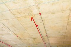 I tubi del metallo in spruzzatore del fuoco e della costruzione sul tubo rosso stanno pendendo dall'interno del soffitto Fotografie Stock Libere da Diritti