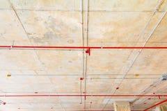 I tubi del metallo in spruzzatore del fuoco e della costruzione sul tubo rosso stanno pendendo dall'interno del soffitto Fotografie Stock