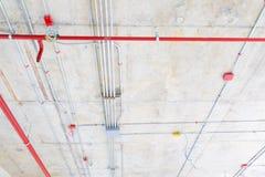 I tubi del metallo in spruzzatore del fuoco e della costruzione sul tubo rosso stanno pendendo dall'interno del soffitto Immagine Stock