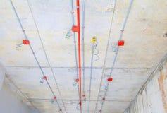 I tubi del metallo in spruzzatore del fuoco e della costruzione sul tubo rosso stanno pendendo dall'interno del soffitto Immagini Stock