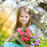 I tulipani adorabili della tenuta della bambina per sua madre in ciliegia fanno il giardinaggio Fotografia Stock Libera da Diritti