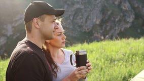 I turisti bevono il tè da una tazza del termos sui precedenti delle montagne video d archivio