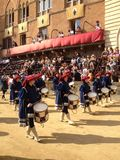 I turisti che guardano il costume tradizionale variopinto ed operato sfoggia all'ippica, Palio di Siena, tenuto nel quadrato medi Fotografie Stock Libere da Diritti