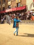 I turisti che guardano il costume tradizionale variopinto ed operato sfoggia all'ippica, Palio di Siena, tenuto nel quadrato medi Fotografie Stock