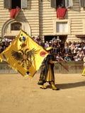 I turisti che guardano il costume tradizionale variopinto ed operato sfoggia all'ippica, Palio di Siena, tenuto nel quadrato medi Immagini Stock
