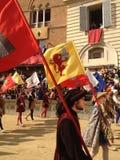 I turisti che guardano il costume tradizionale variopinto ed operato sfoggia all'ippica, Palio di Siena, tenuto nel quadrato medi Fotografia Stock