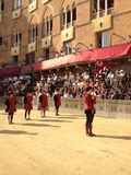 I turisti che guardano il costume tradizionale variopinto ed operato sfoggia all'ippica, Palio di Siena, tenuto nel quadrato medi Fotografia Stock Libera da Diritti
