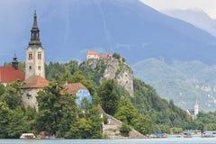 I turisti che visitano la chiesa di vnebovzetja di Cerkev Marijinega nell'isola nel centro del lago hanno sanguinato Immagine Stock
