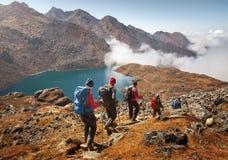 I turisti del gruppo con gli zainhi discende giù sulla traccia di montagna du Fotografia Stock Libera da Diritti