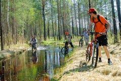 I turisti della bicicletta vanno lungo la strada sommersa Immagini Stock Libere da Diritti