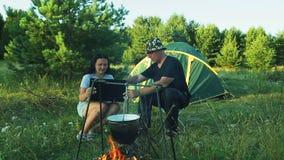 I turisti della donna e dell'uomo stanno sedendo alla tenda, guardando il vaso appendere sopra il fuoco e lavorare al computer po video d archivio