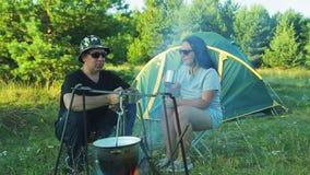 I turisti della donna e dell'uomo stanno sedendo alla tenda, tè bevente e stanno guardando il vaso appendere sopra il fuoco stock footage