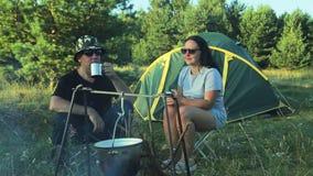 I turisti della donna e dell'uomo stanno sedendo alla tenda, tè bevente e stanno guardando il vaso appendere sopra il fuoco archivi video