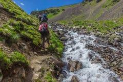 I turisti della montagna salgono la collina lungo il fiume turbolento nelle montagne di Caucaso Fotografia Stock