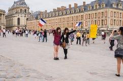 I turisti delle giovani donne posano per la macchina fotografica dell'amico a Versailles immagini stock