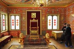 I turisti esaminano il trono in grande palazzo di legno Fotografia Stock
