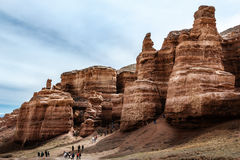 I turisti esplorano le rocce rosse nel canyon di Charyn Immagine Stock